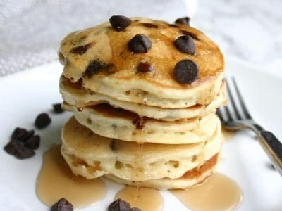 chocolate chip pancakes stacked on a white plate