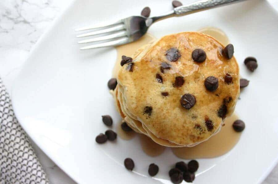 overhead view of chocolate chip pancakes stacked on a white plate