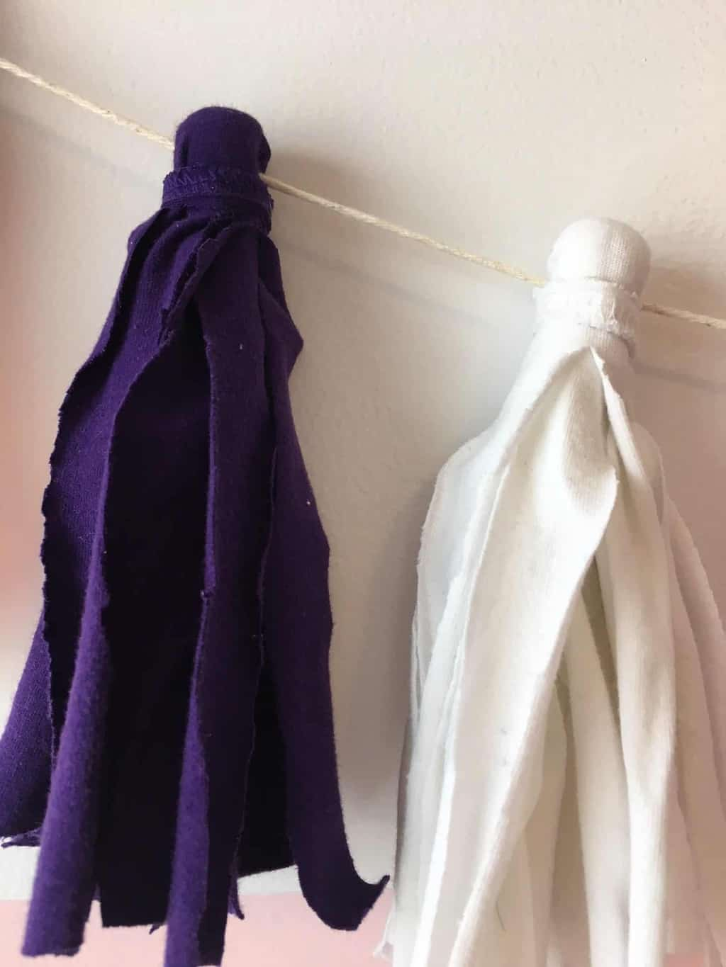purple and white fabric tassels hanging from cream colored string