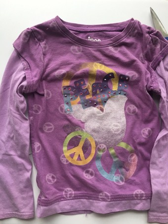purple long sleeve child's shirt with peace signs on front