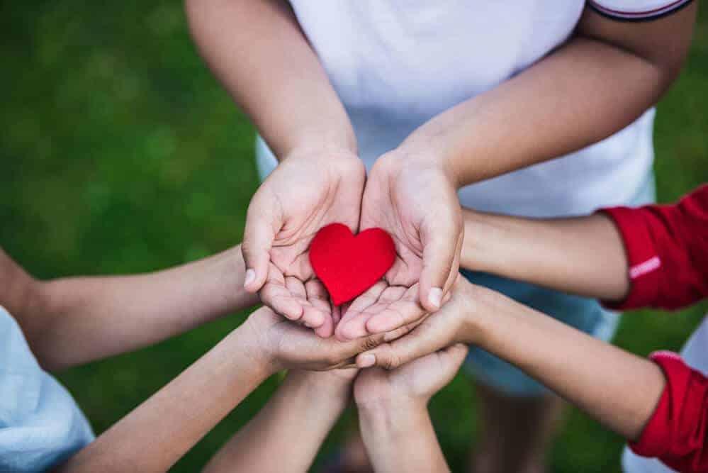kids hands holding a paper heart