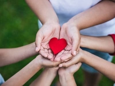 group of kids holding a paper heart