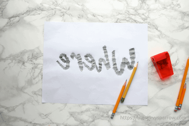 white paper with pencil marks where printed letters are on reverse side