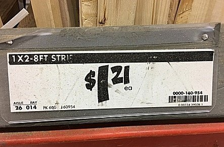 "Home Depot shelf tag for 1""x2"" boards with price of $1.21"