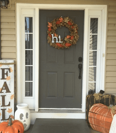 front porch decorated for fall with a burlap fall wreath and a fall sign