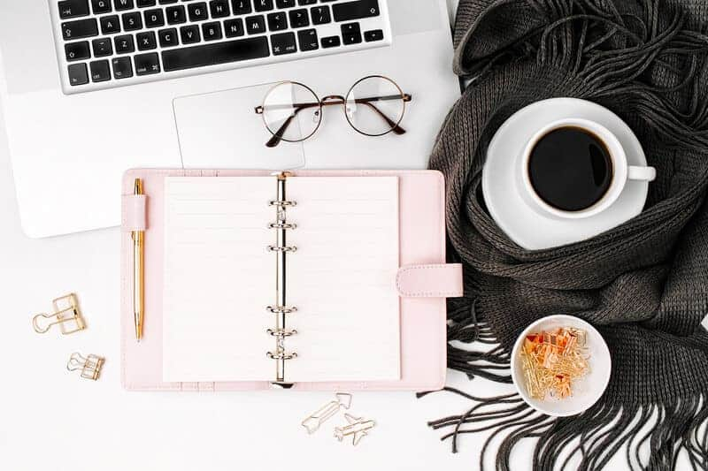 pink planner on a desk with computer and coffee