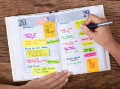 woman writing in a planner with important dates highlighted