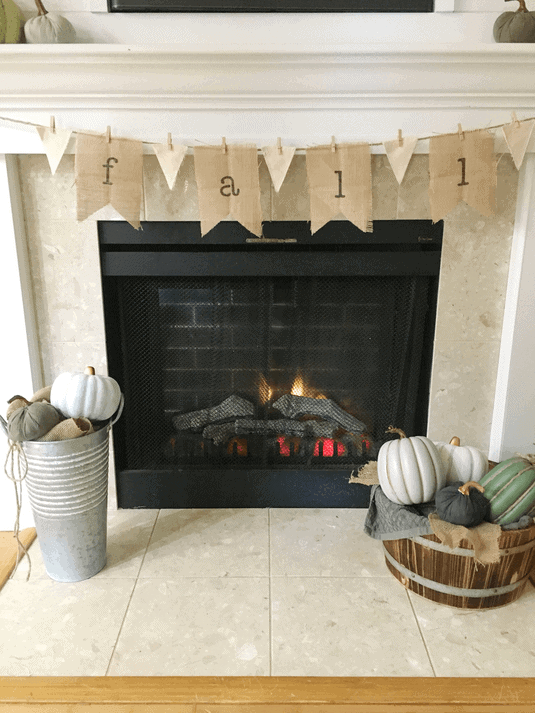 DIY burlap banner that says fall hung on a fireplace mantel