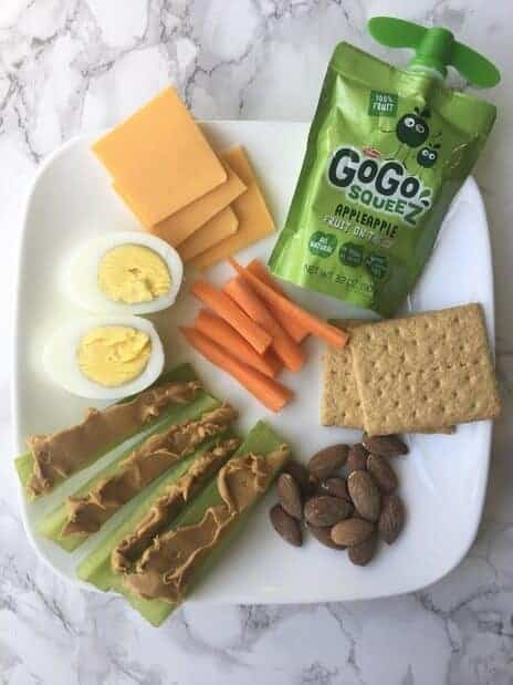 snack plate with hard boiled eggs, celery, carrots, graham crackers, and apple sauce