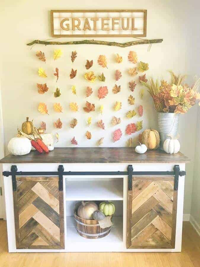 DIY fall leaf wall decor hanging above a buffet table