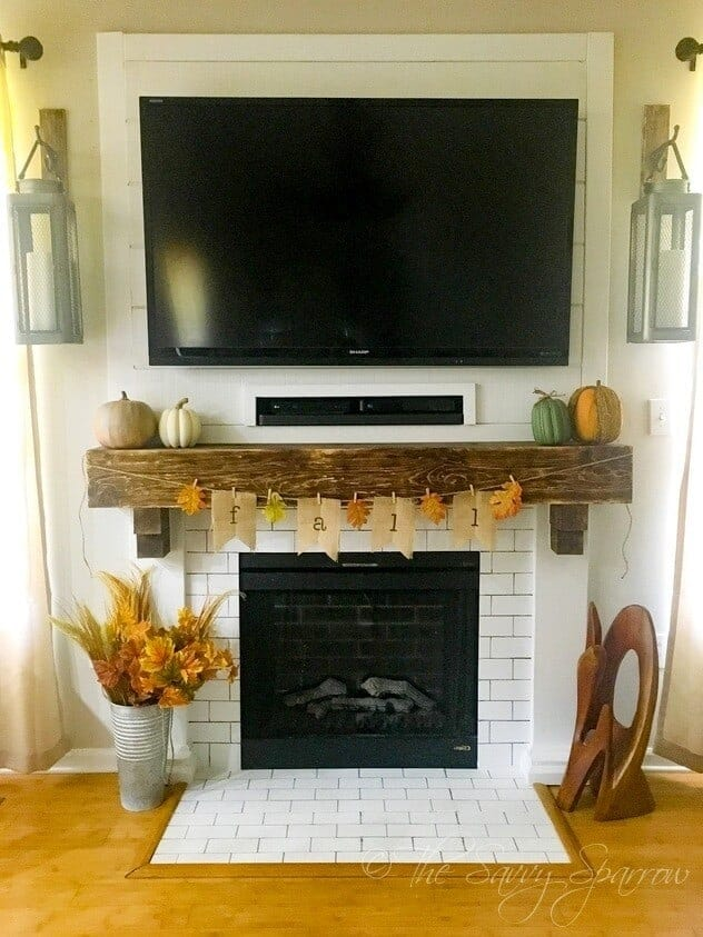 fireplace mantel decorated for fall with pumpkins and a fall burlap banner