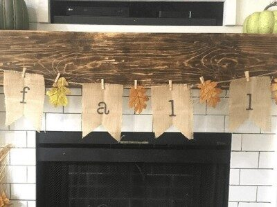 DIY burlap banner that says fall hanging on a fireplace mantel