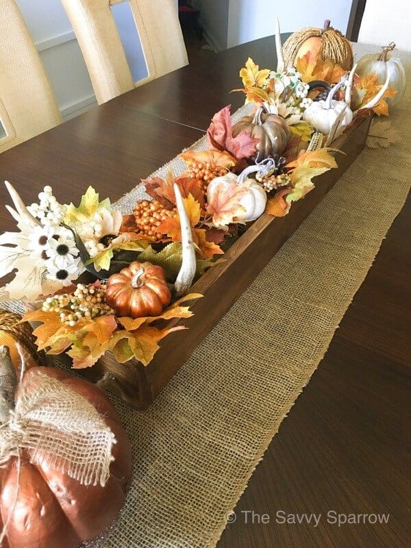 DIY fall centerpiece with pumpkins and flowers on a table