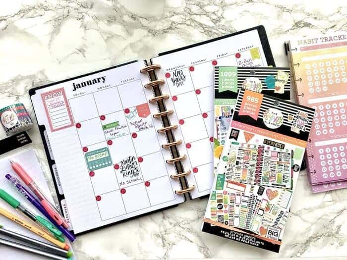 open Happy Planner on a desk with Happy Planner accessories including stickers, habit trackers, washi tape and planner pens