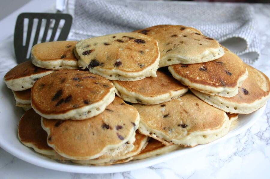 big batch of mini chocolate chip pancakes on a large plate
