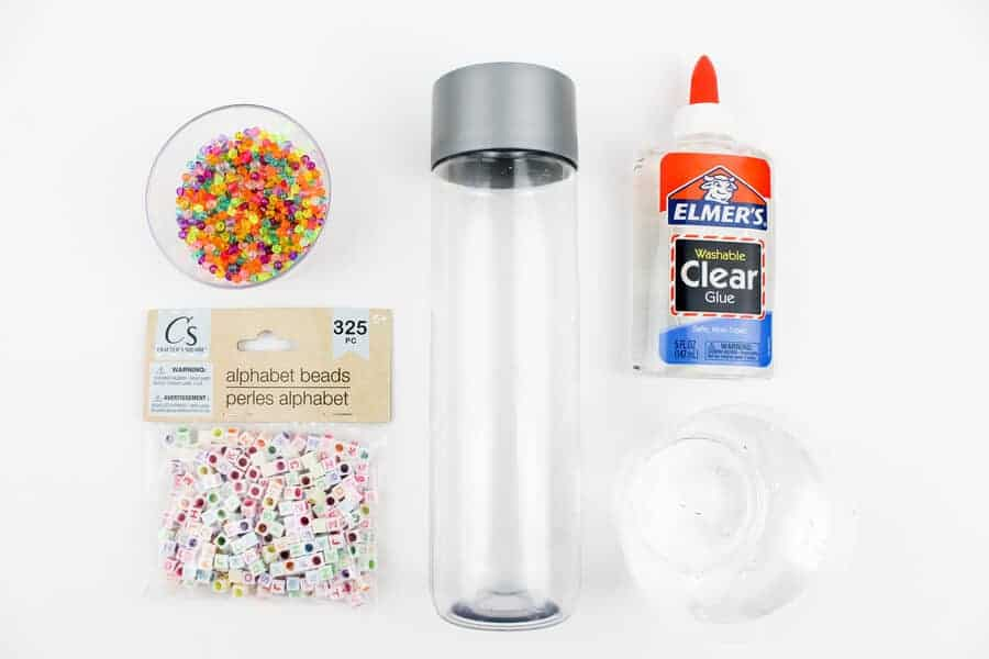 DIY sensory bottles supplies including water bottle, beads, glue, and water