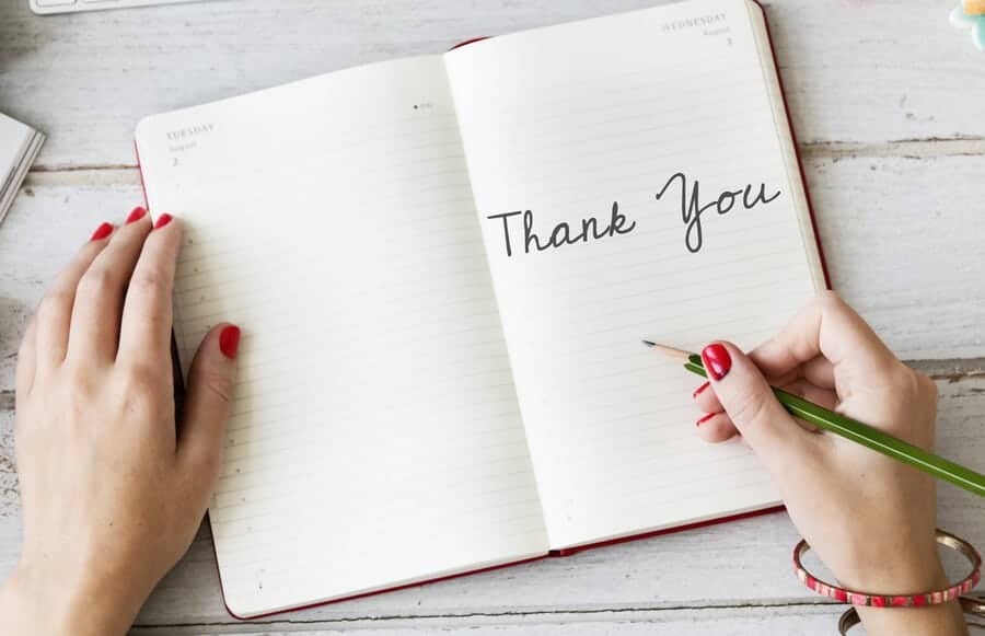 woman's hands writing Thank You in a journal