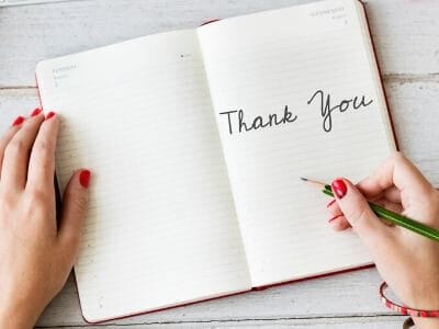 "lady's hands writing the words ""Thank You"" in a journal"