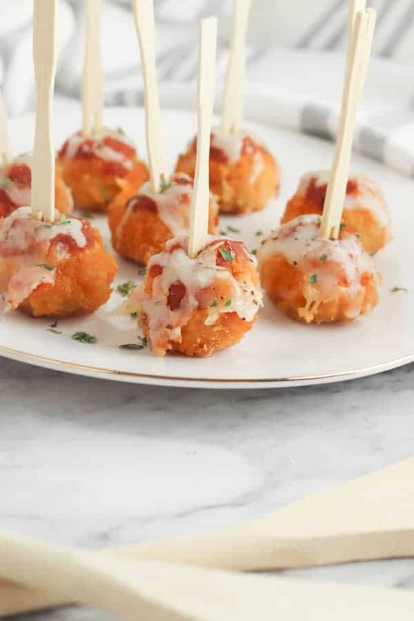 appetizer chicken parmesan bites with cocktail picks on a plate