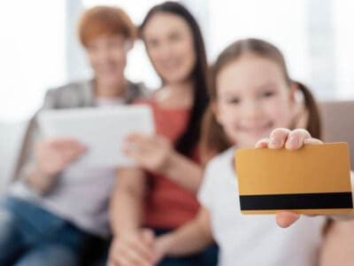 young girl holding a debit card with 2 adults in the background