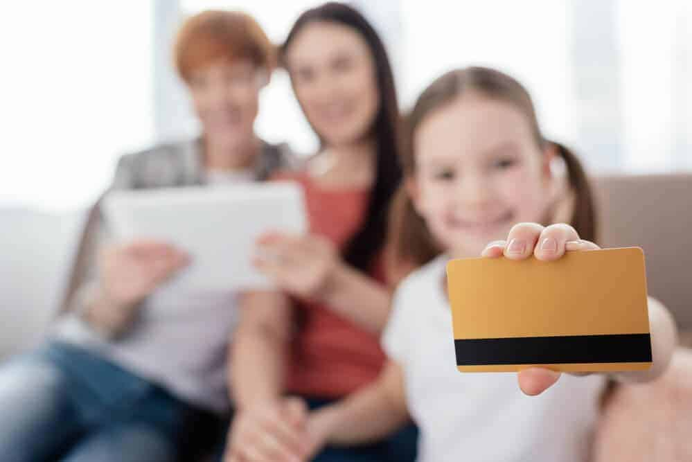 young girl holding debit cards for kids with 2 adults in the background