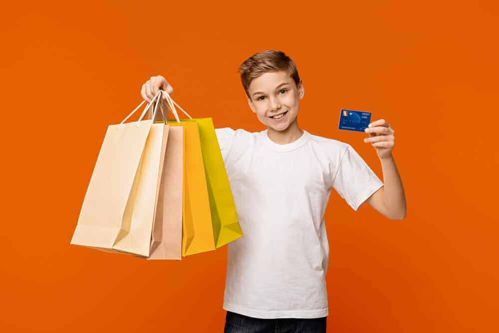 young boy holding debit cards for kids and shopping bags