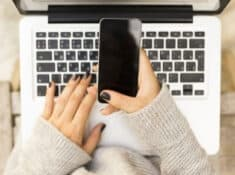 woman's hands holding a phone and typing on a laptop