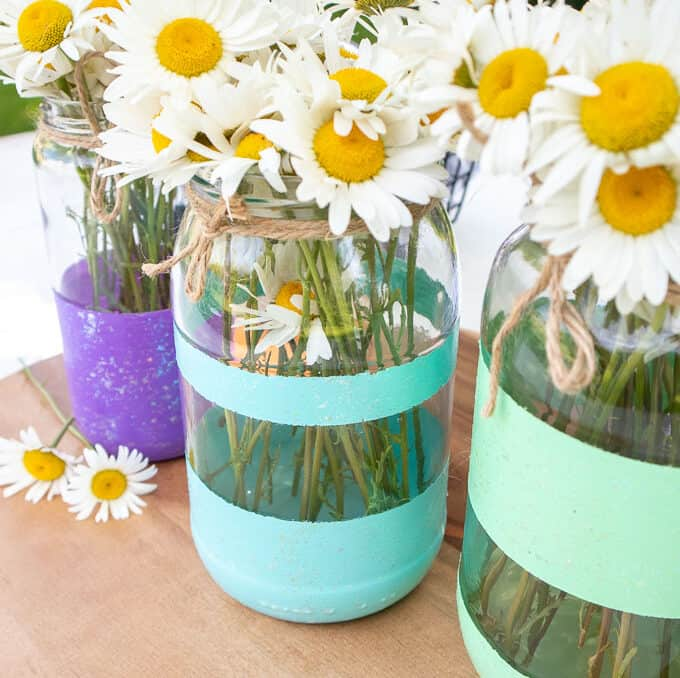 painted stripe mason jars used as vases with daisies inside
