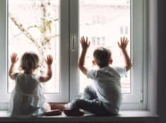 two bored kids looking out a window