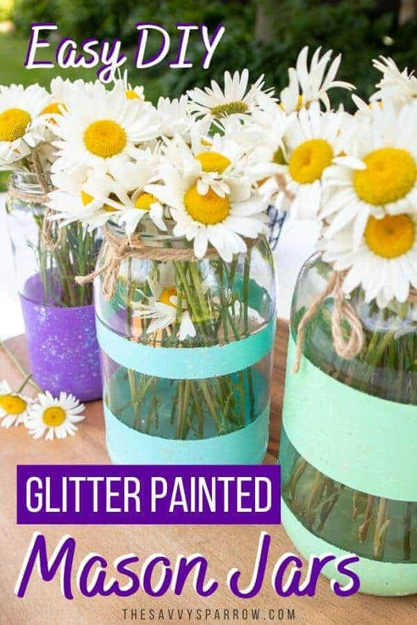 three painted mason jars with glitter stripes on a table with daisies in them