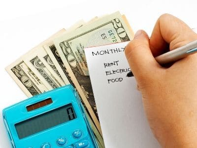 woman writing down monthly bills next to cash and calculator