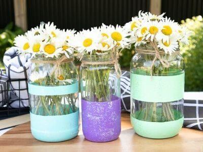 3 glitter mason jar vases with daisies on a table