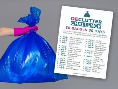 woman's hand holding blue trash bag with decluttering challenge printable checklist