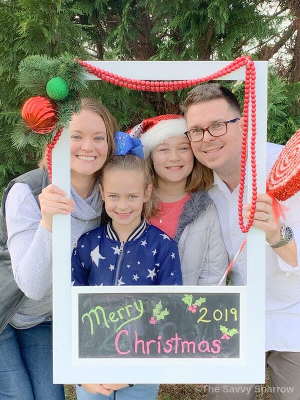 family posing for Christmas photo with a DIY polaroid photo frame