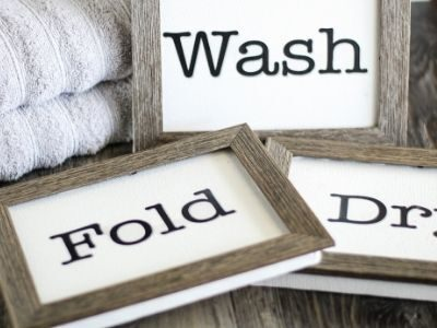 DIY laundry room signs on a table with towels