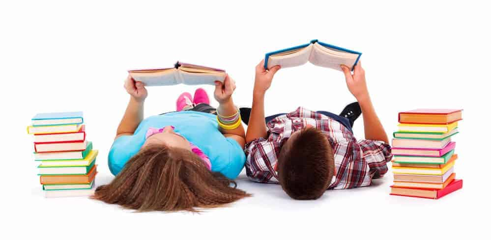 2 kids reading while laying down near a stack of books