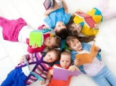 kids laying in a circle on the floor and reading books