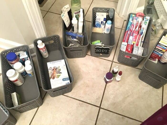 gray storage bins with medicines and toiletries in them