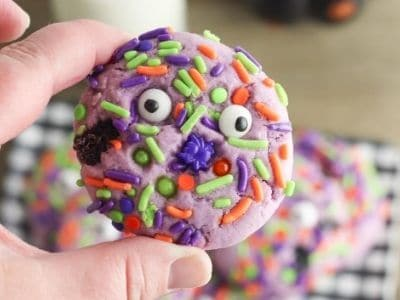 child's hand holding a Halloween cookie with sprinkles