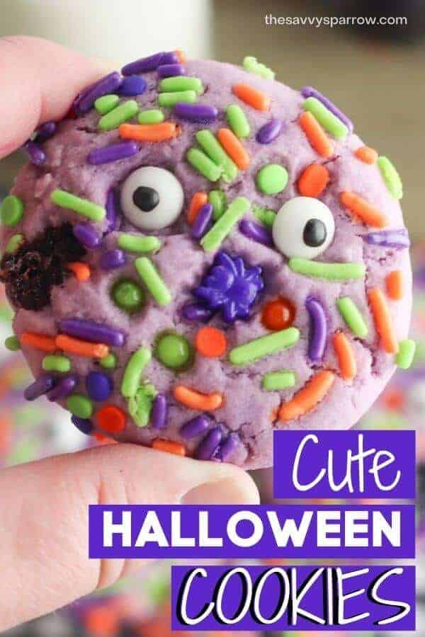 child's hand holding a Halloween cookie with sprinkles with text cute Halloween cookies