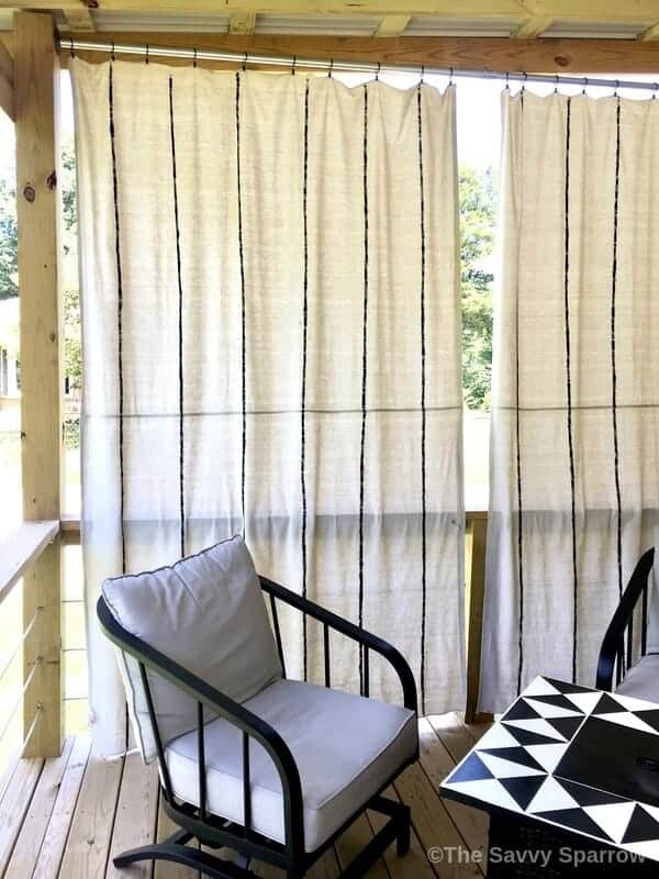 drop cloth curtains hanging on a deck with outdoor furniture