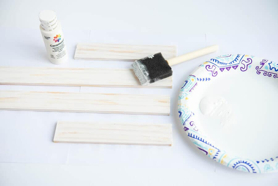cut paint sticks with white paint and foam brush