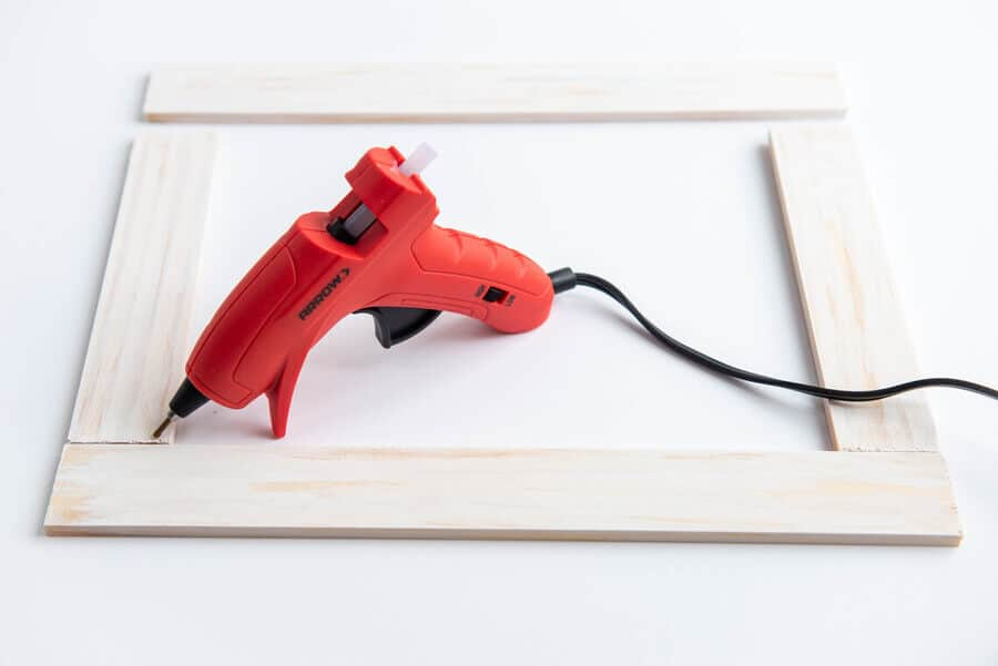 white paint sticks in a rectangle shape on a table with a glue gun
