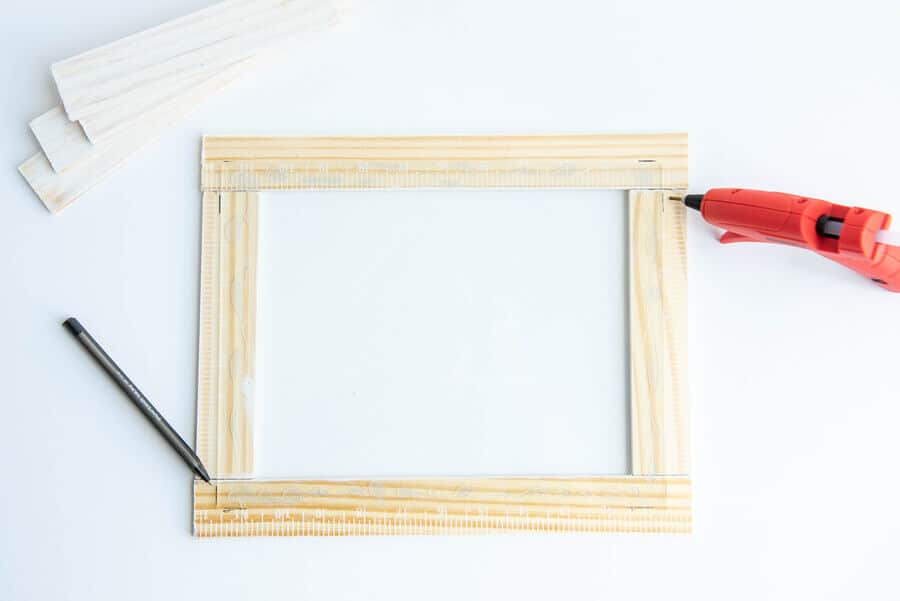 paint sticks in a rectangle shape with glass on top and glue gun