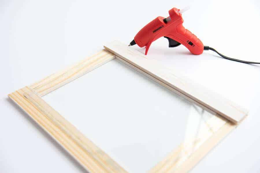 paint sticks and glass hot glued together to make a wood frame
