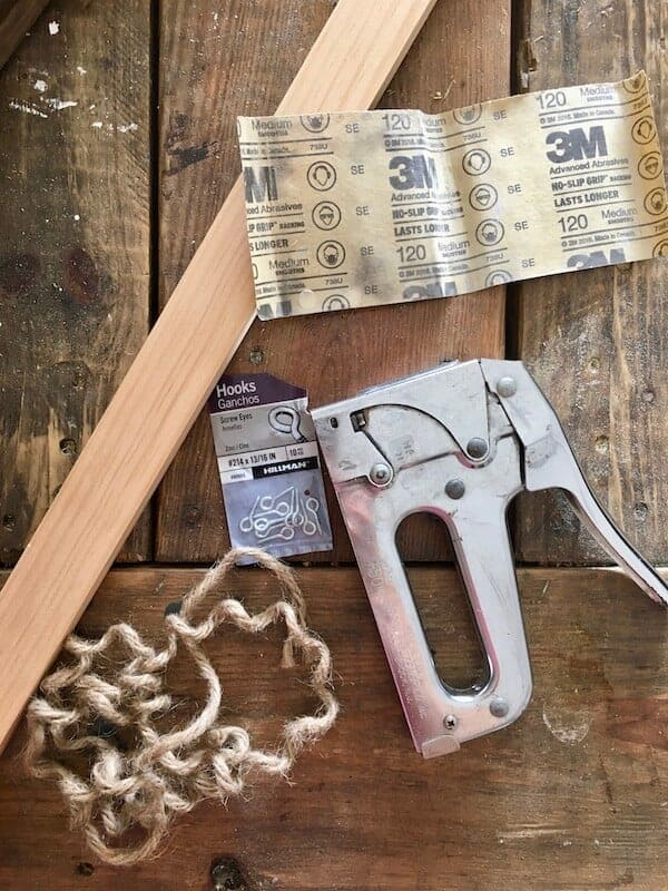 staple gun, eye screws, sand paper, board, and twine on a table