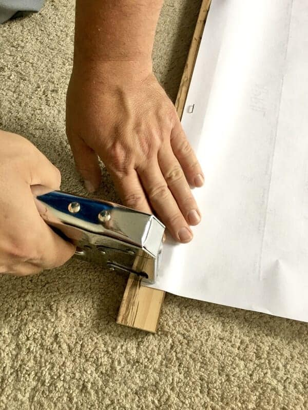 man's hands stapling DIY large wall calendar to board