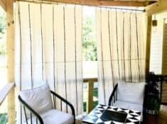 DIY drop cloth curtains hanging on a deck with patio furniture