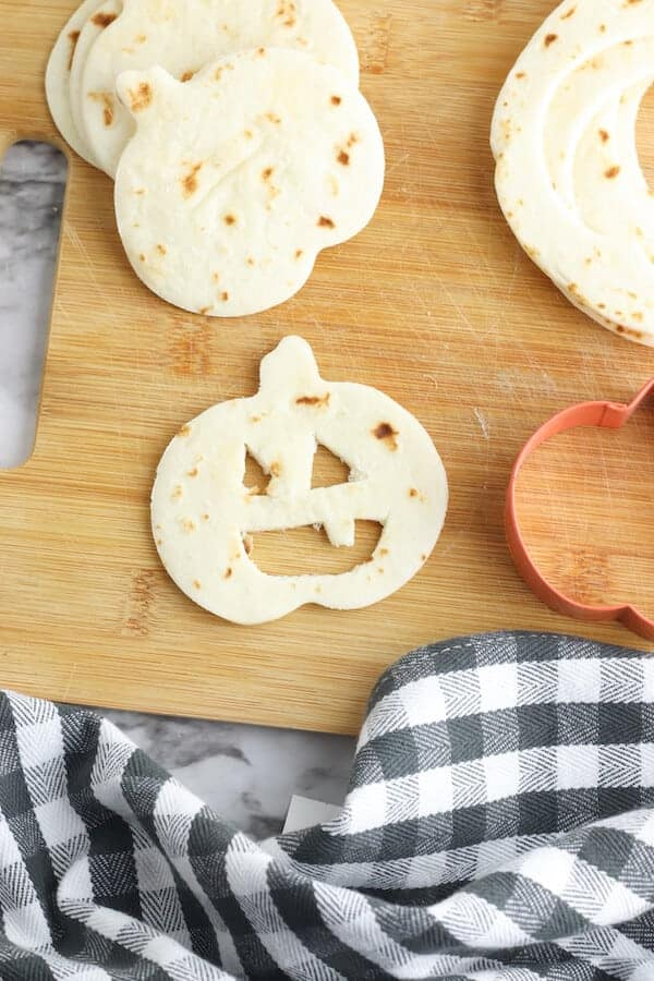 pumpkin shaped tortilla with jack-o-lantern face cut out