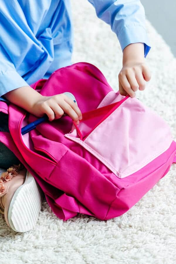 child's hands packing a pink backpack